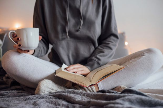 woman-reading-book-and-drinking-tea-on-bed