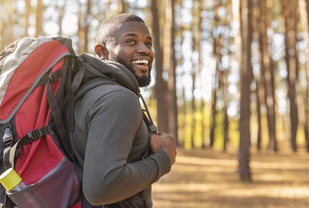 African man wearing backpack standing on forest trail