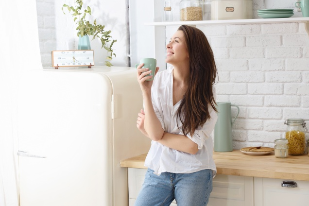 Young happy woman drinking coffee on the kitchen in the morning