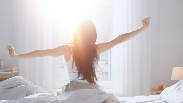 Beautiful Brunette is Waking up in the Morning, Stretches in the Bed, Sun Shines on Her From the Big Window. Happy Young Girl Greets New Day with Warm Sunlight Flare.